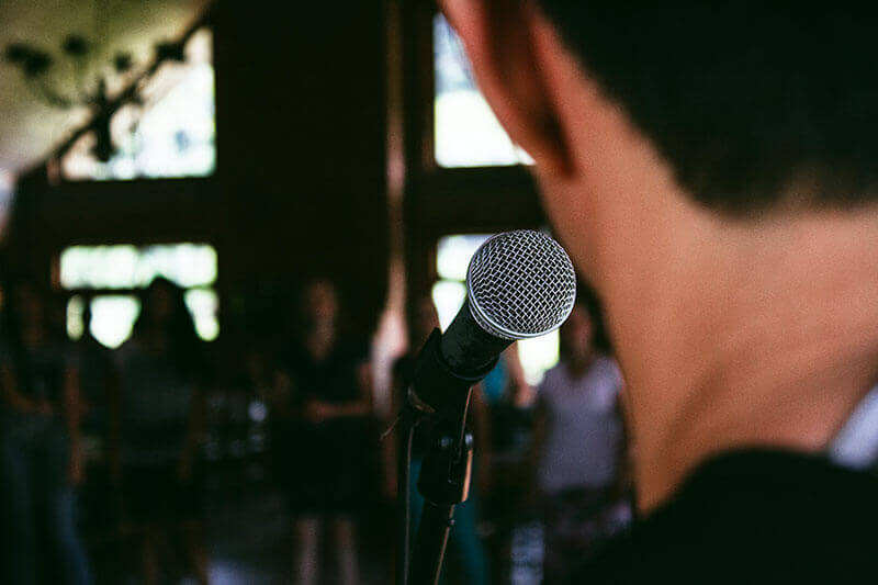 Man behind a microphone speaking to a crowd